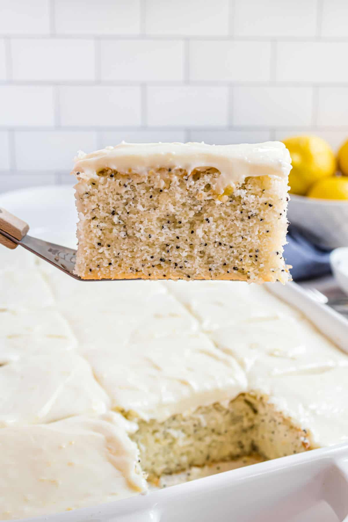 Slice of lemon poppyseed cake on spatula being lifted out of baking pan.