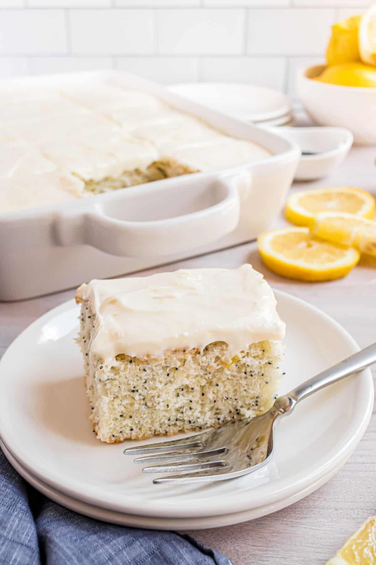 Slice of lemon poppy seed cake on a white plate.