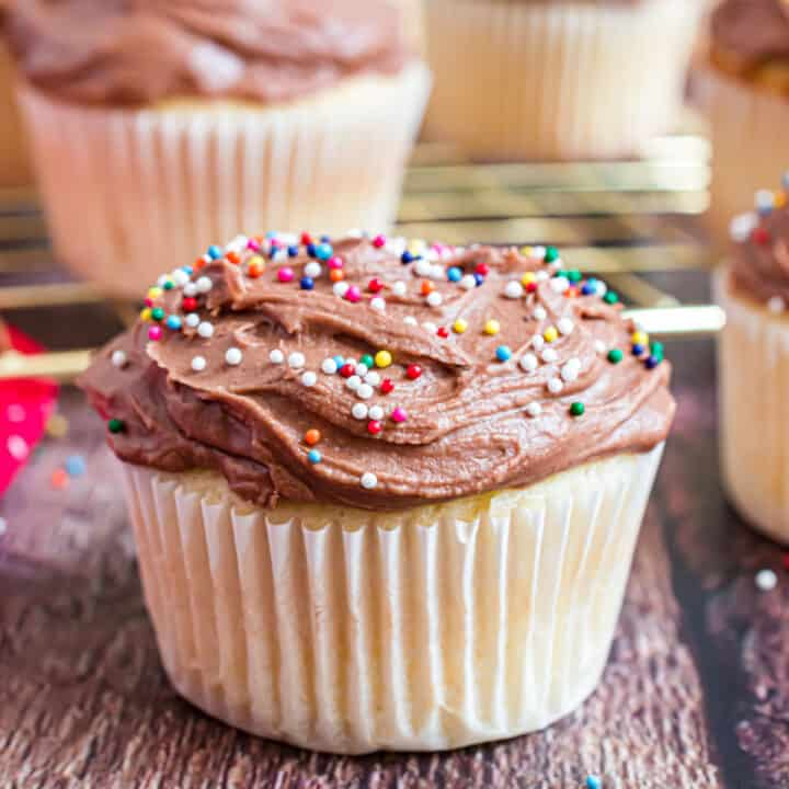 Chocolate frosted yellow cupcake with sprinkles.