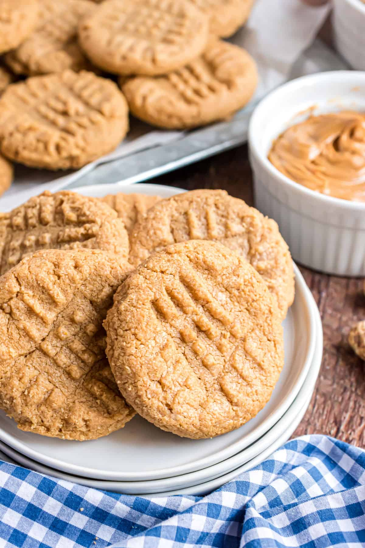 Peanut butter cookies stacked on a white dessert plate.