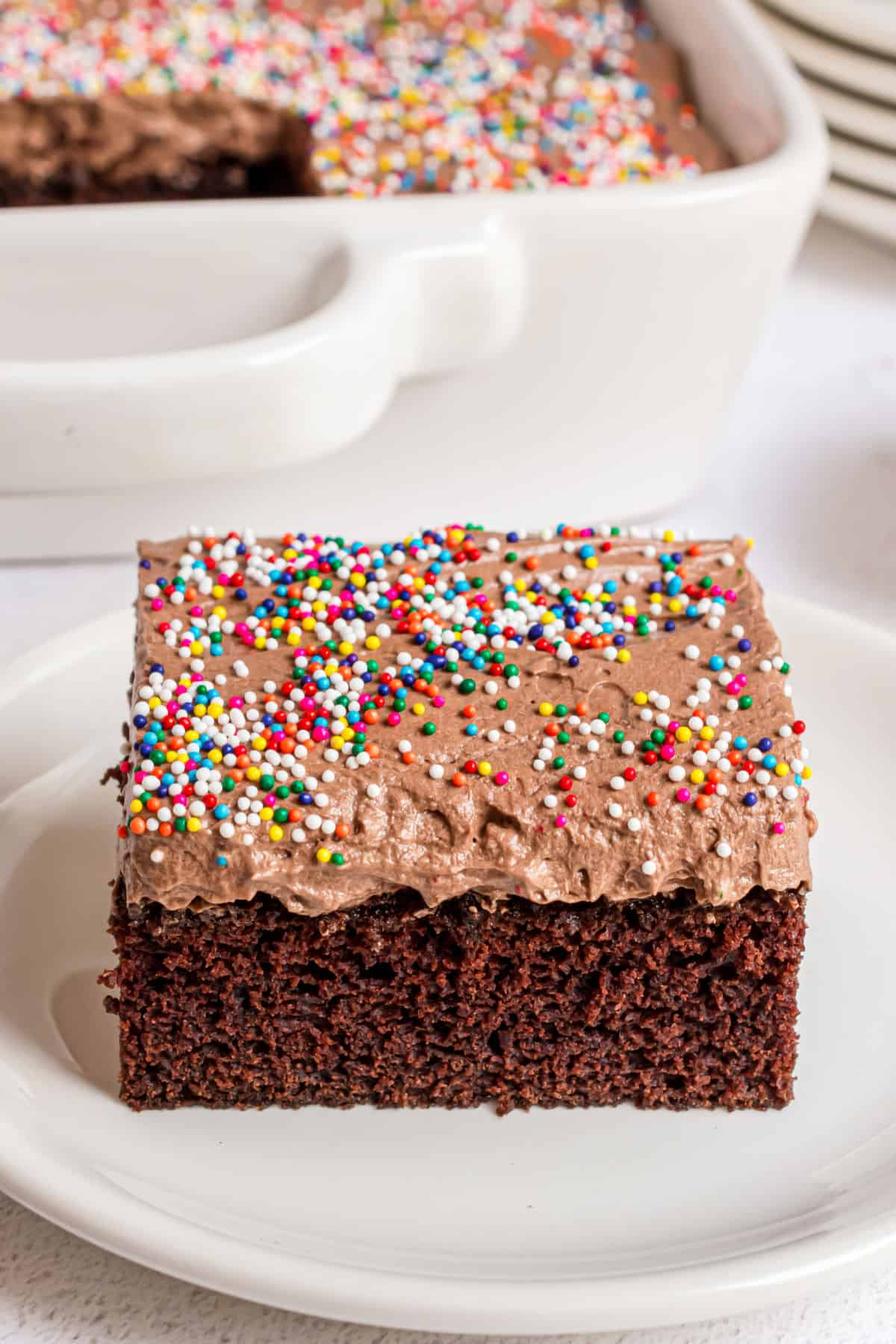 Easy chocolate cake slice on a white plate with sprinkles.