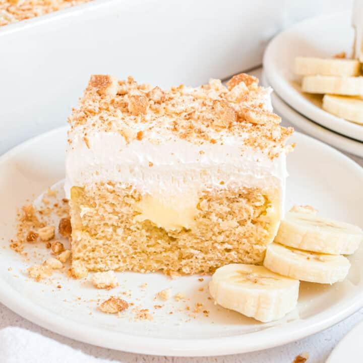 Slice of banana pudding cake with fresh bananas on the side.