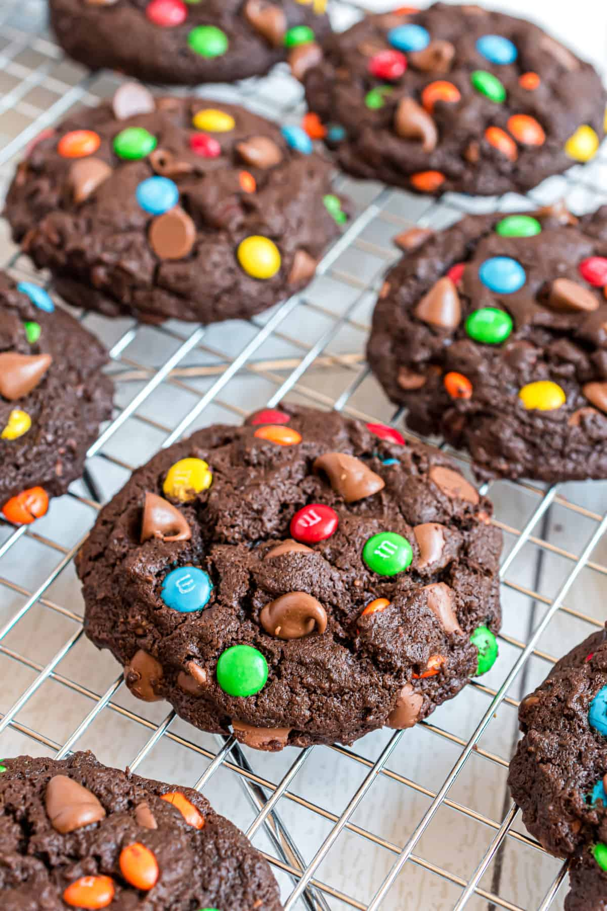 Chocolate cookies with m&m's on a wire cooling rack.