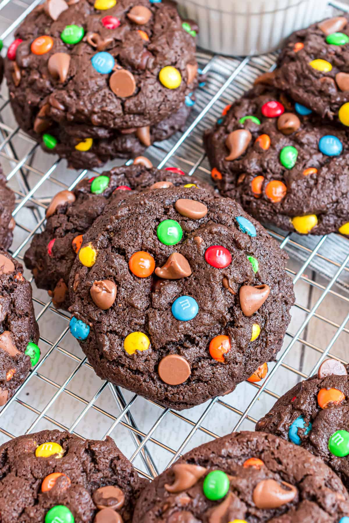 Stacks of chocolate cookies with M&M's on wire cooling rack.