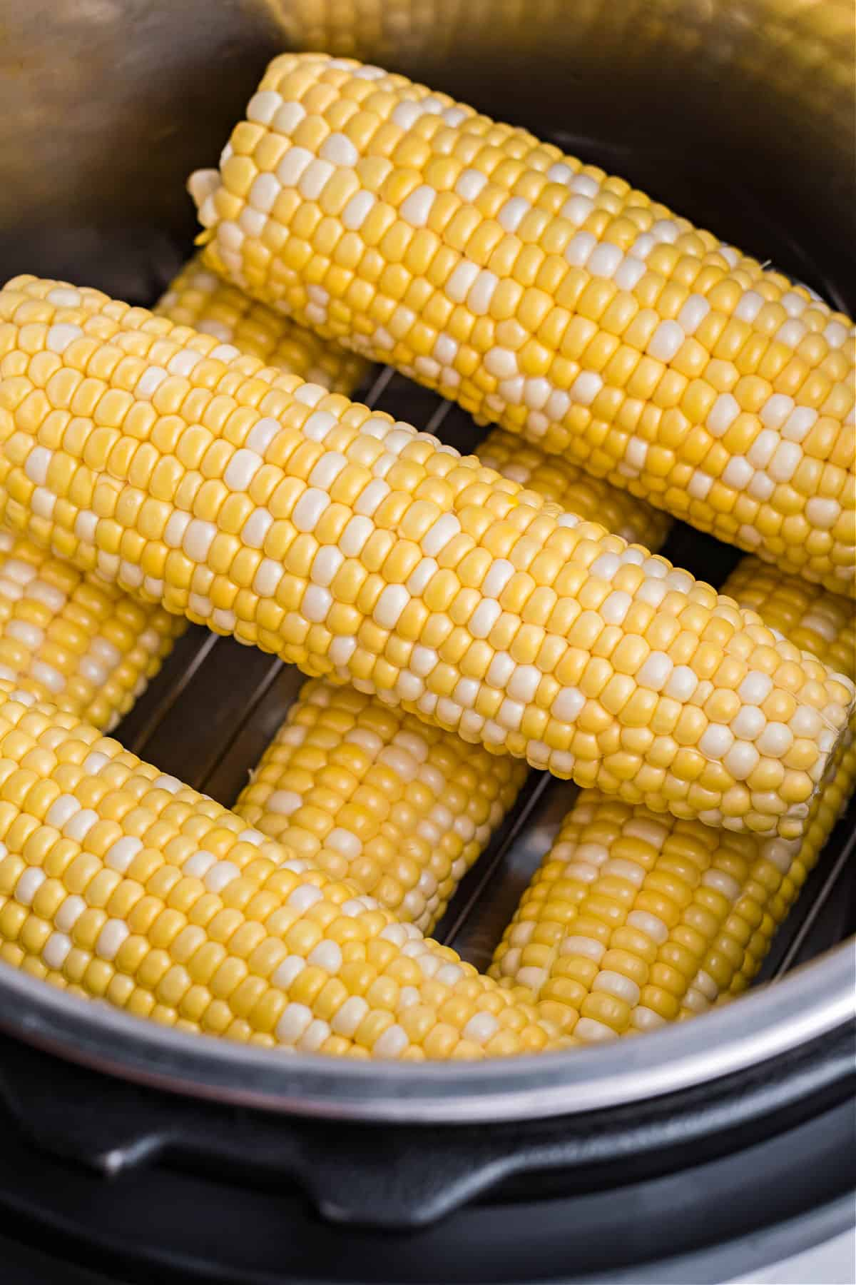 Ears of corn stacked on a trivet inside the instant pot.