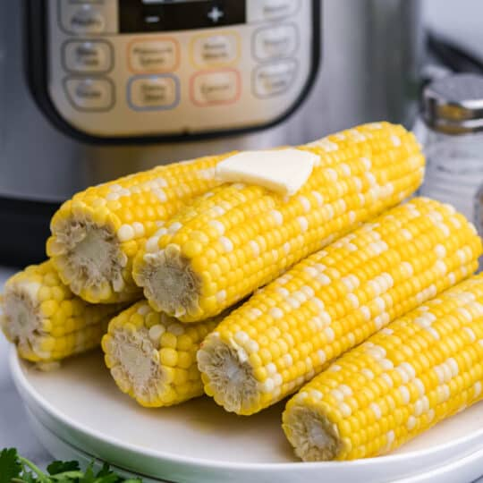 Corn on the cob served on a white plate, stacked on top of each other.