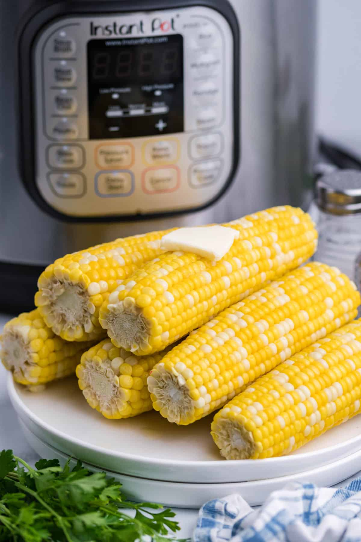 Corn on the cob stacked on a plate with instant pot in background.