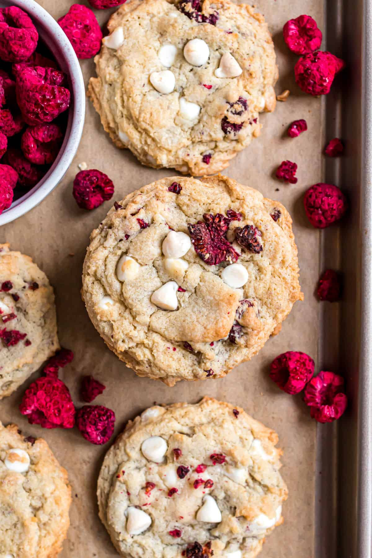Raspberry cheesecake cookies baked on a parchment paper lined cookie sheet.