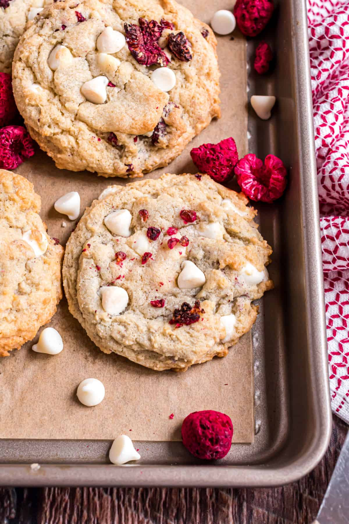 Raspberry cheesecake cookie on parchment paper with white chocolate chips.