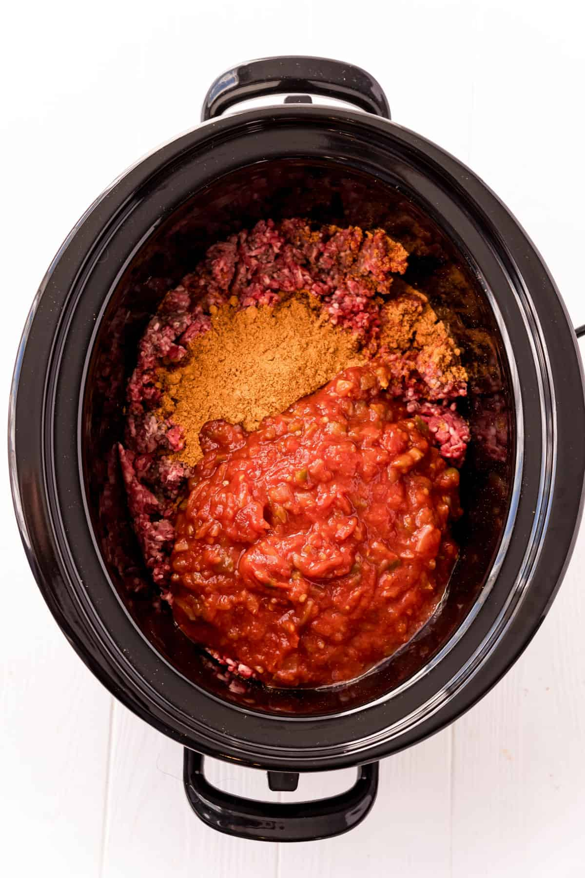 Black slow cooker with ingredients to make taco meat inside.