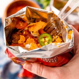 Make the famous fair food at home! This Walking Tacos recipe is a quick and easy meal you can eat on the go. Seasoned beef is mixed into bags of Doritos and topped with your favorite taco fixings!