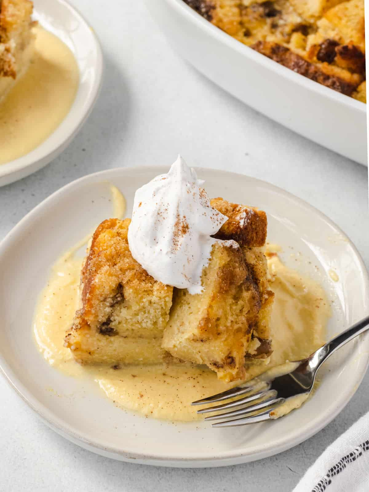 Scoop of apple bread pudding on a plate with vanilla custard and whipped cream.