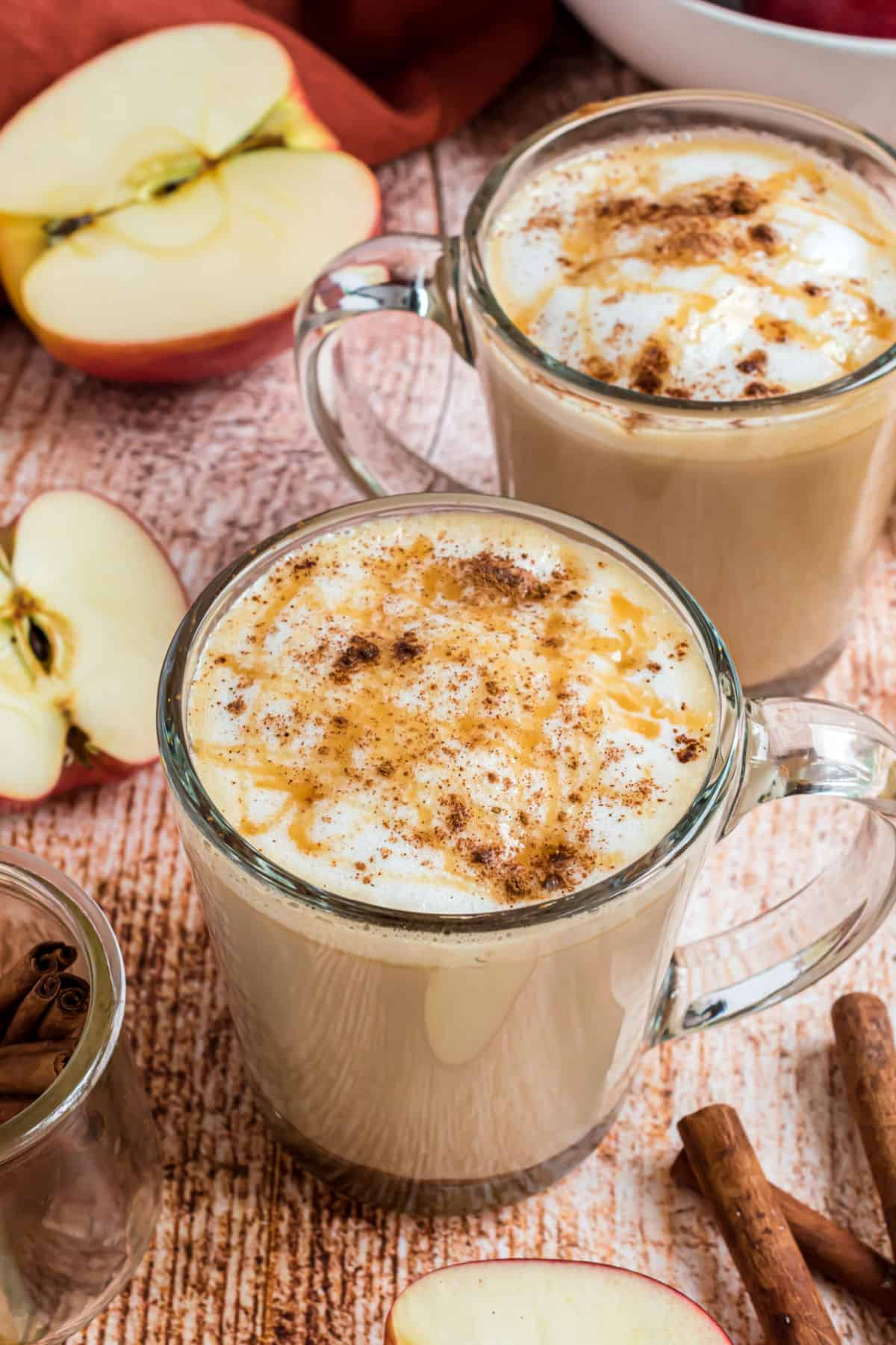 Two clear glass mugs with apple crisp macchiatos topped with caramel syrup.