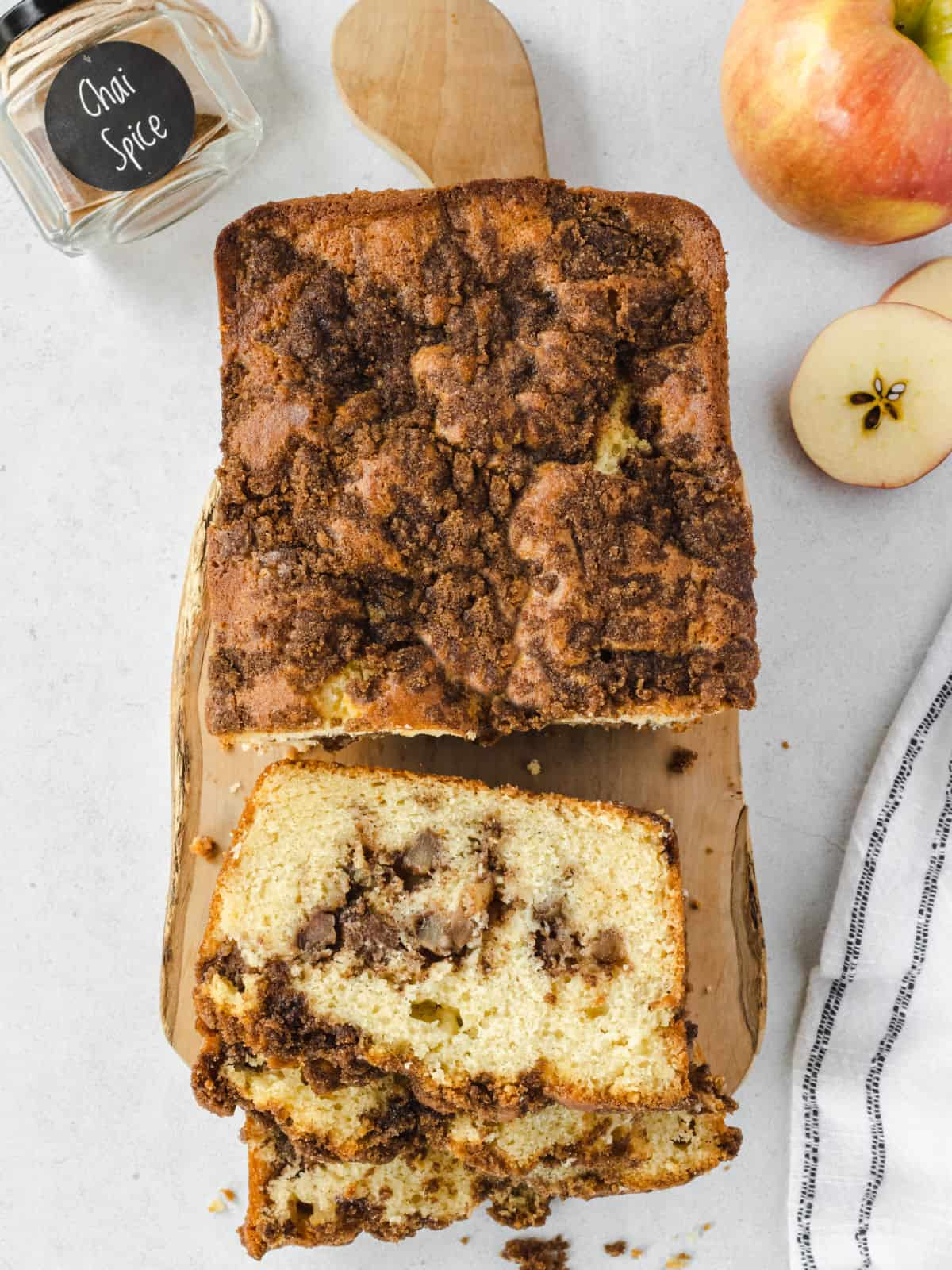 Loaf of apple chai bread sliced on cutting board.