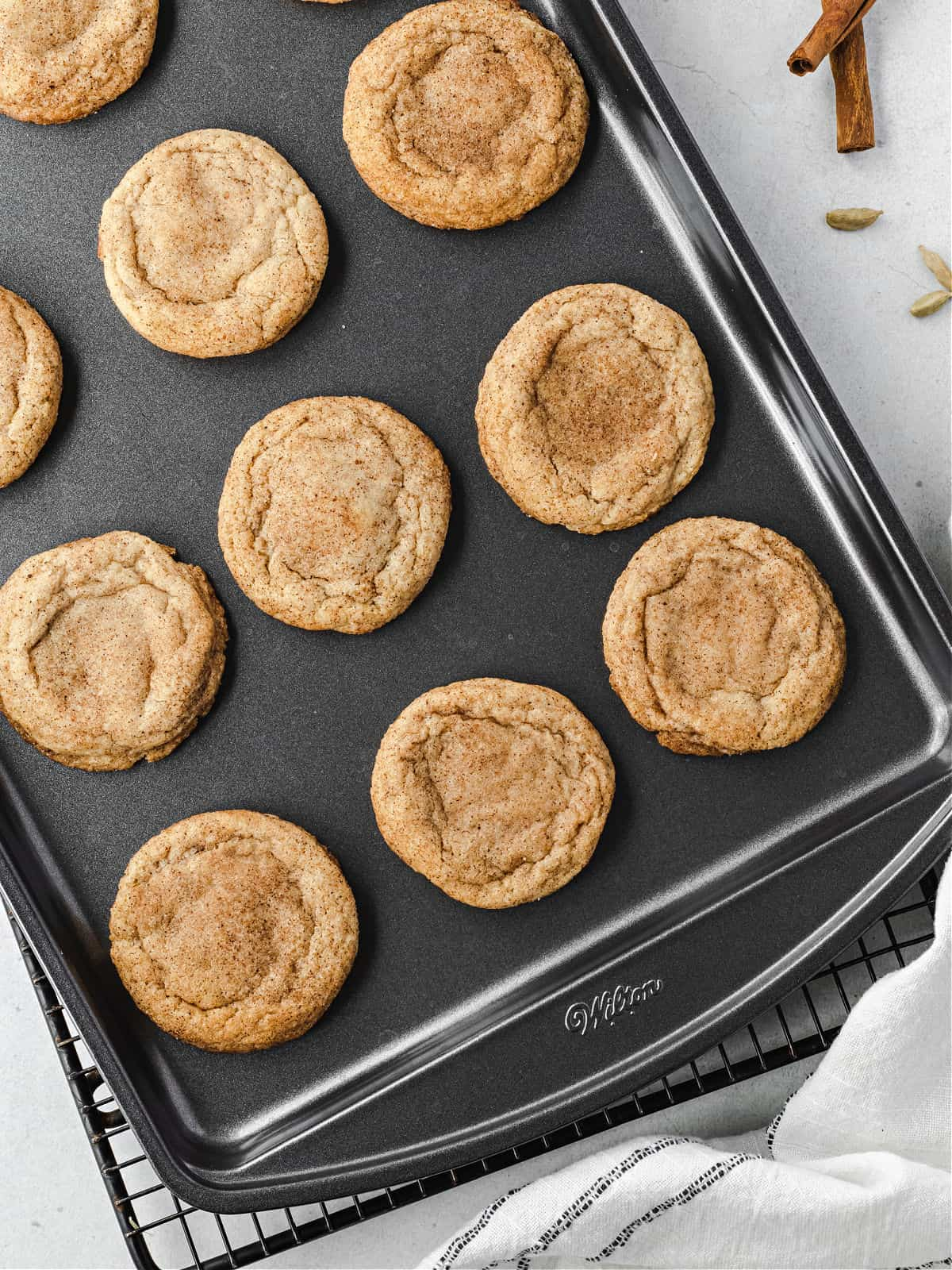 Chai spice cookies on a baking sheet cooling.