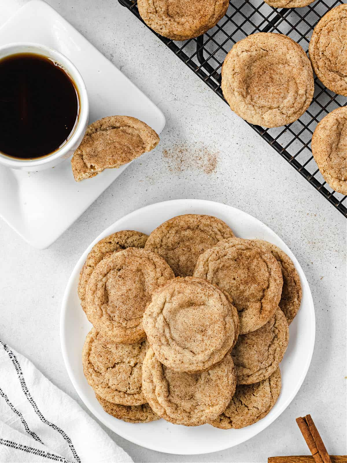 Stack of chai cookies on a plate with a cup of tea in background.