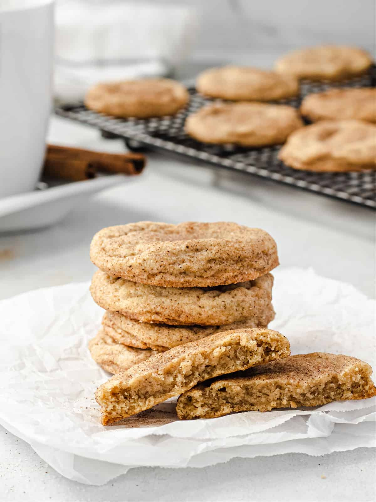 Stack of chai cookies with one broken in half showing chewy texture.