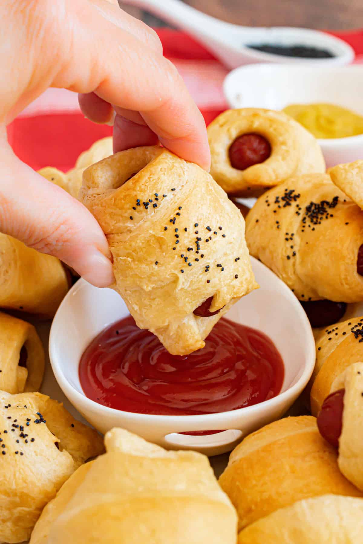 Crescent roll dog being dipped in ketchup.