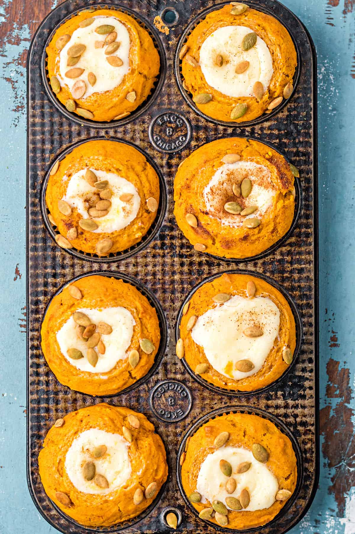 Pumpkin muffins with cream cheese centers and spiced pepitas on top.
