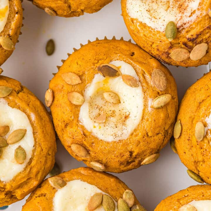Pumpkin Cream Cheese Muffins are a copycat Starbucks treat. Packed with flavor, these muffins have a sweet cream cheese filling and spiced pumpkin seeds sprinkled on top. Easy to make and freezer friendly!