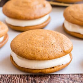 Pumpkin whoopie pie with cream cheese filling on parchment paper.