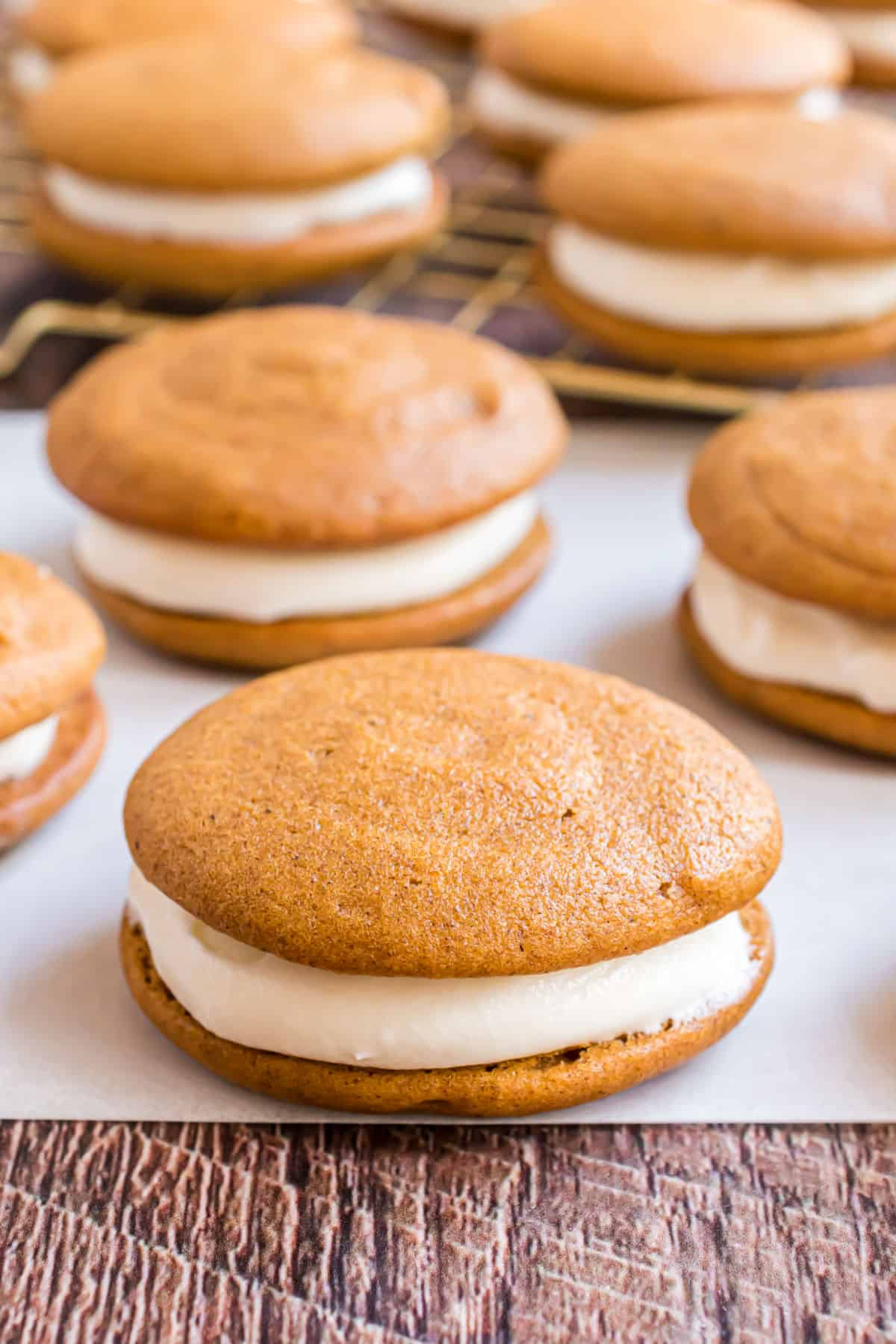 Pumpkin whoopie pies with cream cheese filling on a piece of parchment paper.