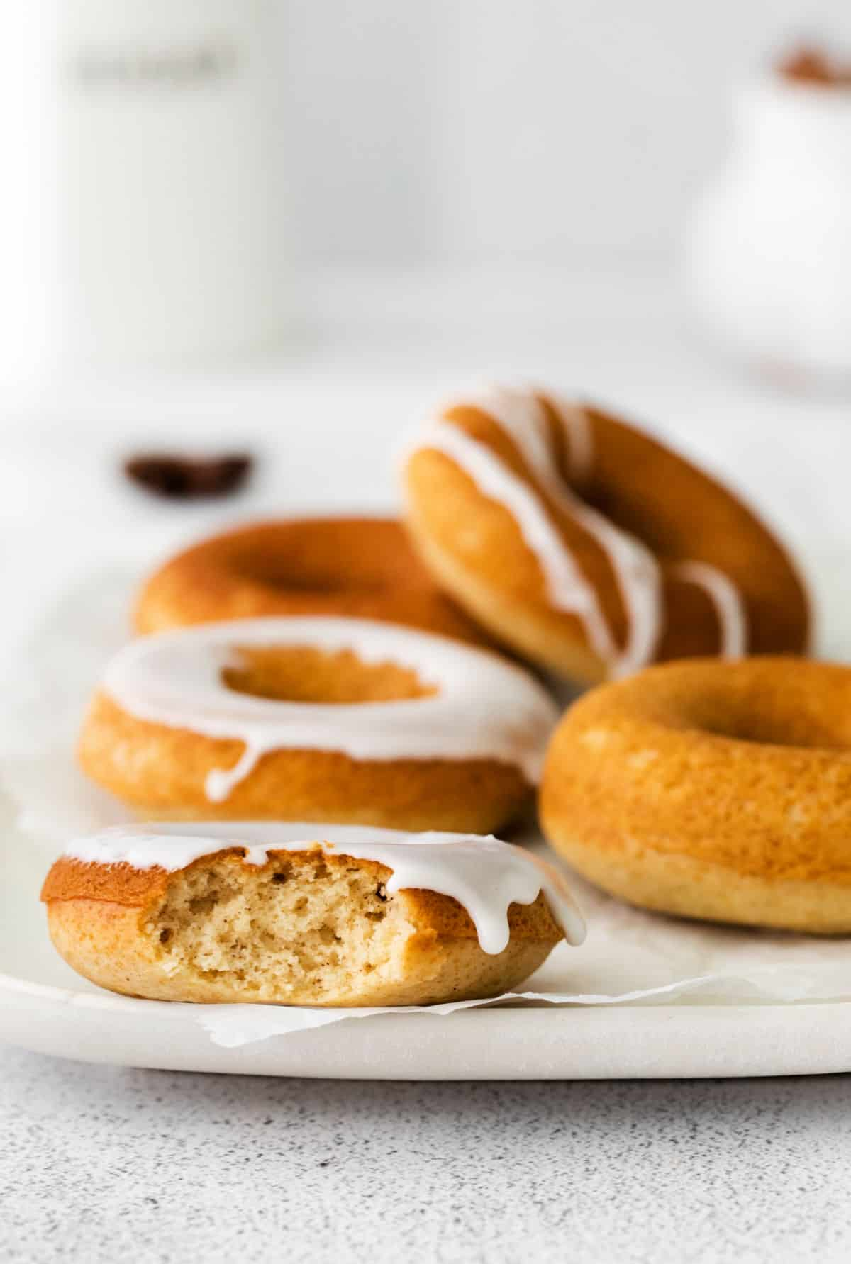 Chai spiced donuts on a plate, drizzled and frosted with vanilla icing.