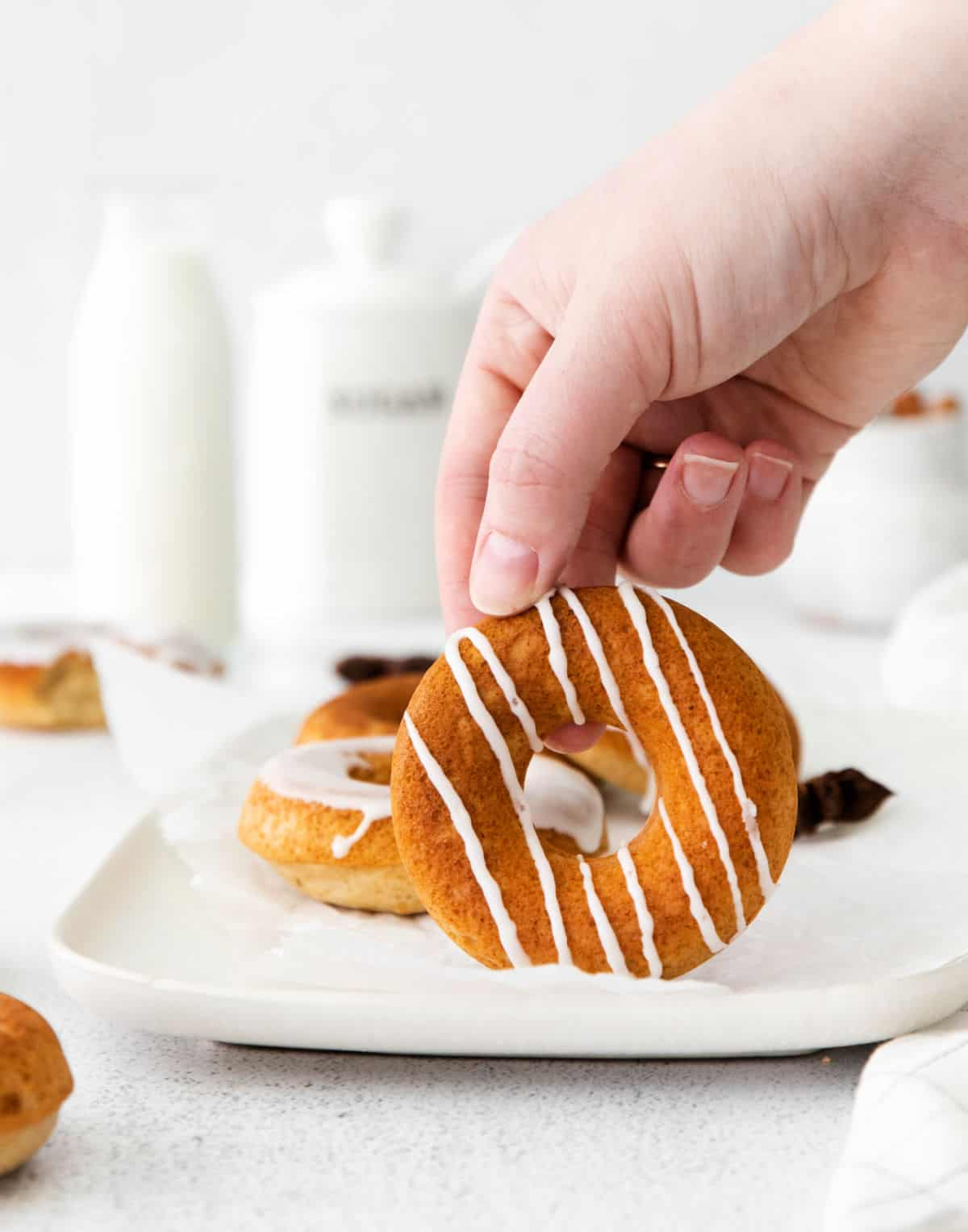 Chai donut with vanilla icing drizzled and a hand picking it up.