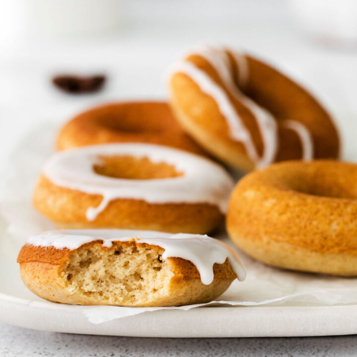 White plate with chai donuts, one bite removed.