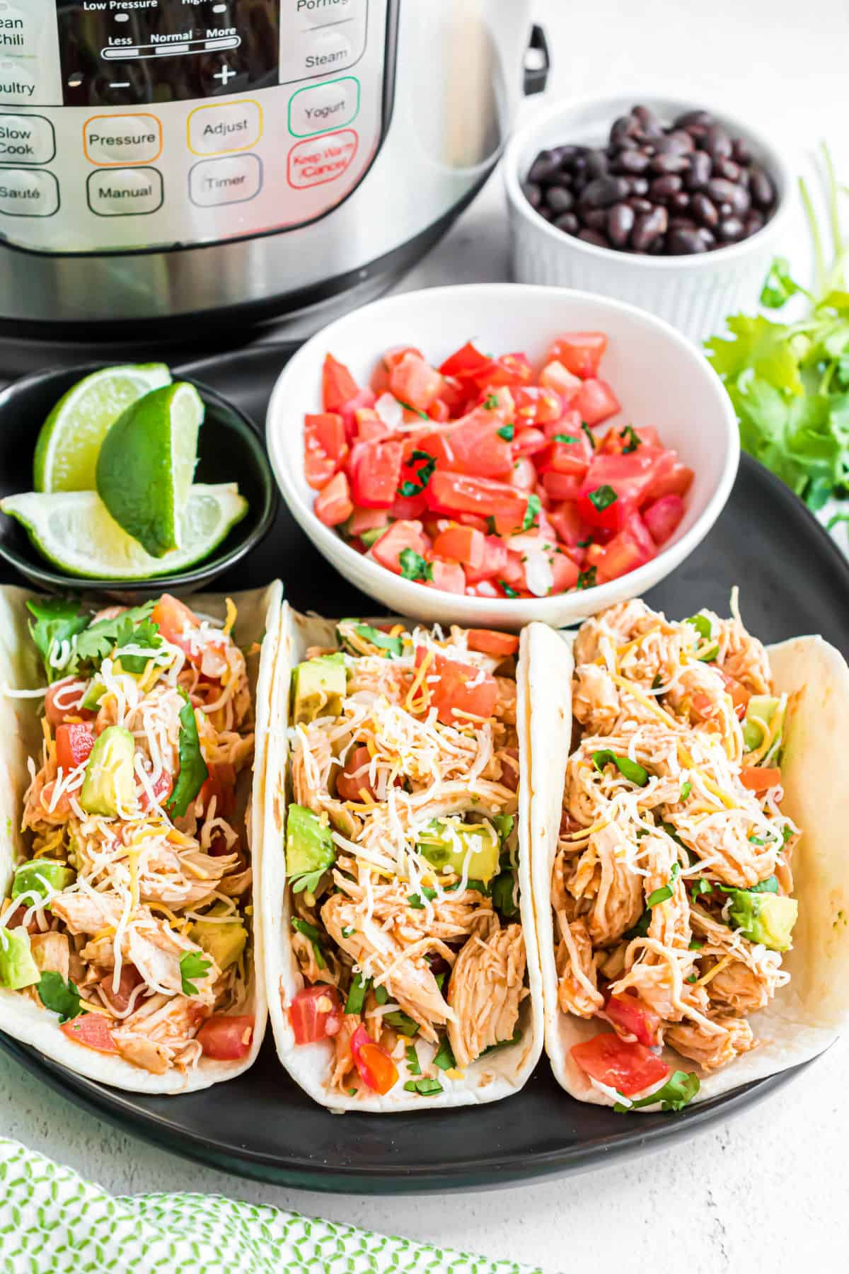 Three chicken tacos with all the fixings and instant pot in background.